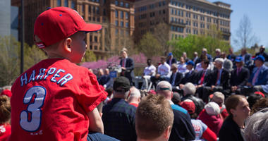 Apr 16, 2019; Philadelphia, PA, USA; A young fan looks on as Philadelphia Phillies owner John Middleton addresses fans and media during an event at Independence Mall to announce Philadelphia as the host of the 2026 All Star Game.