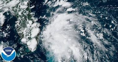 A satellite image shows a tropical depression spinning between the Bahamas and Florida. Depression