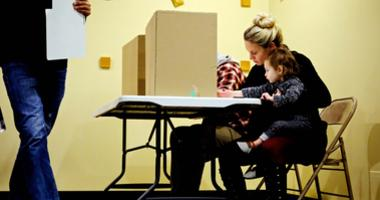 Nov 8, 2016; Frendale, MI, USA; Jenna Townsend, 32, holds her daughter Isla Townsend, 1, as she fills her ballot during the 2016 United States presidential elections at Renaissance Vineyard Church.