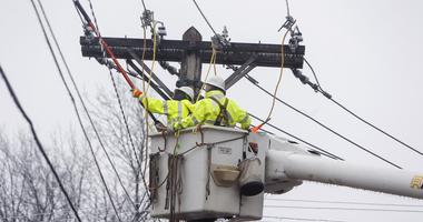Feb 1, 2016; Springfield, MO, USA; Tommy Skinner, left, and Roger Marler, both linemen for PAR Electrical Contractors, ground power lines to prevent any possible feedback so tree limbs can be cut away from the lines and power restored.