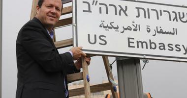 Jerusalem Mayor Nir Barkat poses with a new road sign to the new U.S. Embassy in Jerusalem