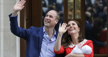 Prince William and Kate, Duchess of Cambridge, wave holding their newborn son