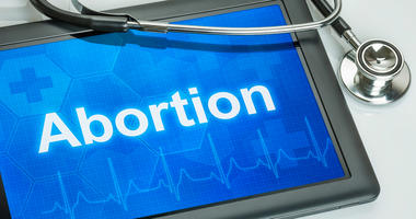 Tablet with the text Abortion on the display