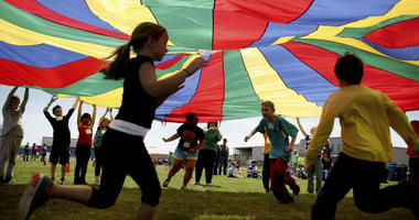 In this Thursday, April 25, 2013 file photo, elementary school third graders run under a rainbow colored tarp during the 15th Annual Kansas Kids Fitness Day, in Hutchinson, Kan.