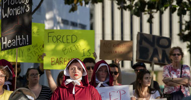 Margeaux Hartline, dressed as a handmaid, protests against a ban on nearly all abortions outside of the Alabama State House in Montgomery, Ala., on Tuesday, May 14, 2019.