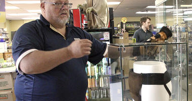 """In this May 2, 2018 file photo, Blockbuster Alaska general manager Kevin Daymude moves a display case featuring the jockstrap worn by actor Russell Crowe in the 2005 movie """"Cinderella Man"""" at a Blockbuster video store in Anchorage, Alaska."""