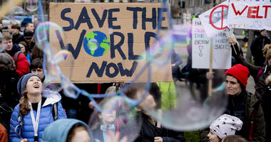 """Young people protest for climate action with a sign reading 'Save the World Now"""" during a  'Friday for Future' demonstration in Berlin, Germany, Friday, March 22, 2019."""