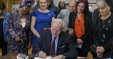 Arkansas Gov. Asa Hutchinson signs a bill into law that replaces two statues in a U.S. Capitol display with statues of civil rights leader Daisy Bates and country musician Johnny Cash, Thursday, April 11, 2019, in Little Rock, Ark. The governor was joined