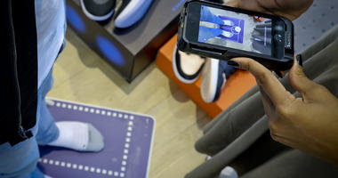 Nike officials demonstrate the company's foot-scanning tool on its app that will measure and remember the length, width and other dimensions of customers' feet after they point a smartphone camera to their toes, Wednesday April 24, 2019, in New York.