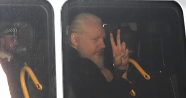 Julian Assange signals his arrival at the Court of Magistrates of Westminster, in London, after agents removed him from the Ecuadorian embassy and arrested him, on Thursday, April 11, 2019.