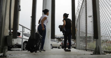 In this June 20, 2018, file photo, sisters from Guatemala seeking asylum, cross a bridge to a port of entry in to the United States from Matamoros, Mexico, in Brownsville, Texas.
