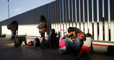 A migrant sits with his children as they wait to hear if their number is called to apply for asylum in the United States, at the border, Friday, Jan. 25, 2019, in Tijuana, Mexico.