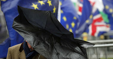 A man shelters with an umbrella as he walks by Pro EU protestors holding flags opposite the Houses of Parliament in London, Thursday, April 4, 2019.