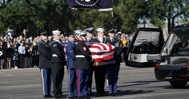 The flag-draped casket of former President George H.W. Bush is carried by a joint services military honor guard to Special Air Mission 41 at Ellington Field during a departure ceremony Monday, Dec. 3, 2018, in Houston.