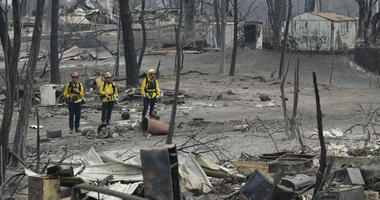 San Bernardino County Fire department firefighters assess the damage to a neighborhood in the aftermath of a wildfire, Sunday, July 29, 2018, in Keswick, Calif.