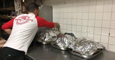 Joe Cacia prepares to load the bakery's massive brick oven with Thanksgiving turkeys.