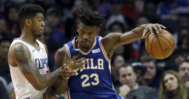 Philadelphia 76ers guard Jimmy Butler, right, protects the ball from Los Angeles Clippers guard Tyrone Wallace during the first half of an NBA basketball game in Los Angeles, Tuesday, Jan. 1, 2019.
