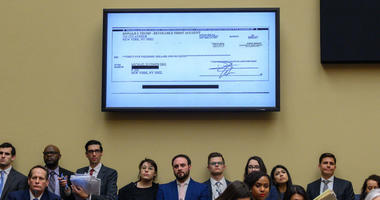 A copy of a check paid to Michael Cohen by President Trump's trust is displayed as Michael Cohen, former lawyer for President Donald Trump, testifies before the House Oversight and Reform Committee on Capitol Hill in Washington, D.C., on February 27, 2019