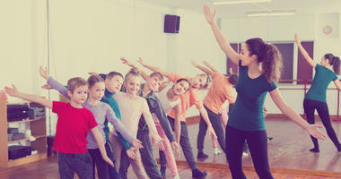 Boys and girls studying contemp dance in dancing studio