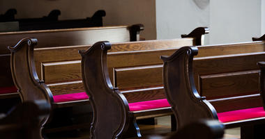 Empty wooden benches in old Catholic Church