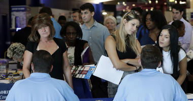 In this June 21, 2018, file photo, job applicants talks with representatives from Aldi at a job fair hosted by Job News South Florida, in Sunrise, Fla. On Friday, Oct. 5, the U.S. government issues the September jobs report.