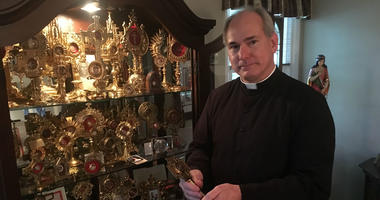 Father Jason Kulczynski, pastor of Holy Martyrs Church in Oreland, Montgomery County, displays some of the relics which are going on public exhibit on Thursday to mark the Roman Catholic All Saints Day.
