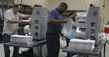 Election workers place ballots into electronic counting machines, Sunday, Nov. 11, 2018, at the Broward Supervisor of Elections office in Lauderhill, Fla.