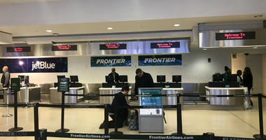 The Frontier Airlines check-in counter is shown at Philadelphia International Airport.