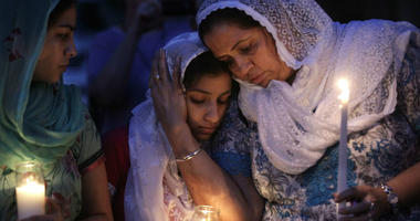 In this Monday, Aug. 6, 2012 file photo, Sikh worshipers gather for a candlelight vigil after prayer services at the Sikh Religious Society of Wisconsin in Brookfield, Wis.