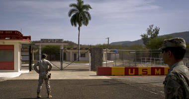 an Army soldier, right, and a Marine stand in front of the gates that separate the Cuban side from the Guantanamo Bay U.S. Naval Base