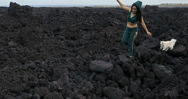 In this Monday, April 22, 2019 photo, Tisha Montoya and her dog Bebe cut through the lava field that covered much of her property and destroyed her home near Pahoa, Hawaii.