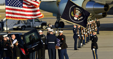 The flag-draped casket of former President George H.W. Bush is carried by a joint services military honor guard to a hearse at Andrews Air Force Base in Md., Monday, Dec. 3, 2018.