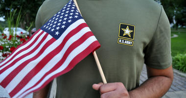 In this July 3, 2018, file photo, a Pakistani recruit, 22, who was recently discharged from the U.S. Army, holds an American flag as he poses for a picture.