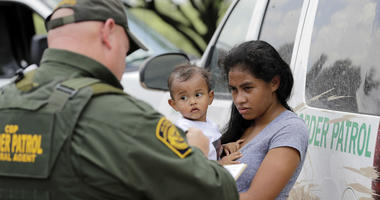 A mother migrating from Honduras holds her 1-year-old child as surrendering to U.S. Border Patrol agents after illegally crossing the border Monday, June 25, 2018, near McAllen, Texas.