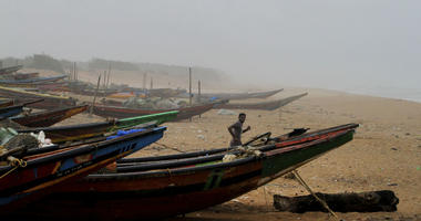 An Indian fisherman runs between the docked fishing boats amid strong winds at Chandrabhaga beach in Puri district of eastern Odisha state, India, Thursday, May 2, 2019.