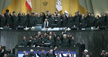 Wearing the uniform of the Iranian Revolutionary Guard, lawmakers chant slogans during an open session of parliament in Tehran, Iran, Tuesday, April 9, 2019.