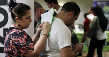 In this Jan. 30, 2018, file photo, Loredana Gonzalez, of Doral, Fla., fills out a job application at a JobNewsUSA job fair in Miami Lakes, Fla.