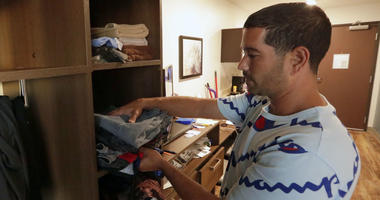 In this Monday, Sept. 10, 2018, photo, Jose Santiago checks on items in the kitchenette in his room at the WoodSpring Suites in Orlando, Fla.