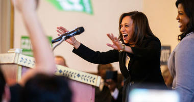 """Sen. Kamala Harris, D-CA, waves to supporters while being welcomed on stage by Deidre DeJear during a \""""All Hands on Deck\"""" event on Tuesday, Oct. 23, 2018, at Old Brick in Iowa City."""
