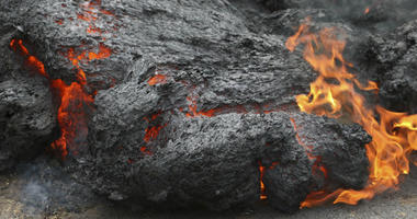 In this May 5, 2018, file photo, lava burns across a road in the Leilani Estates subdivision near Pahoa, Hawaii.
