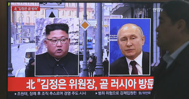 A man passes by a TV screen showing images of North Korean leader Kim Jong Un, left, and Russian President Vladimir Putin, right, during a news program at the Seoul Railway Station in Seoul, South Korea, Tuesday, April 23, 2019.