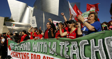 In this Dec. 15, 2018, file photo, United Teachers Los Angeles leaders are joined by thousands of teachers as they march past the Walt Disney Concert Hall downtown Los Angeles.