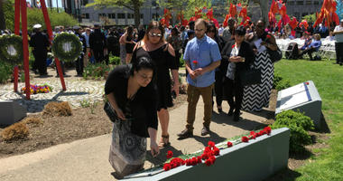 Loved ones lay flowers at the Living Flame Memorial at Franklin Square Park in Philadelphia.