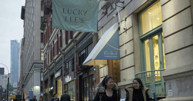 In this Thursday, April 11, 2019 photo, pedestrians walk past the Lucky Lee's restaurant in the Greenwich Village neighborhood of New York.