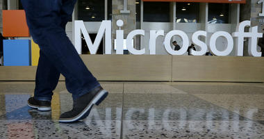 In this April 28, 2015, file photo, a man walks past a Microsoft sign set up for the Microsoft BUILD conference at Moscone Center in San Francisco.
