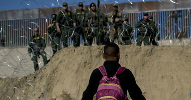 A Honduran migrant converses with U.S border agents on the other side of razor wire after they fired tear gas at migrants pressuring to cross into the U.S. from Tijuana, Mexico, Sunday, Nov. 25, 2018.