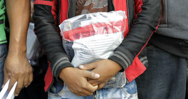 In this Friday, June 22, 2018, file photo, a young immigrant holds his belongings in a Homeland Security bag while waiting to enter the bus station after being processed and released by U.S. Customs and Border Protection, in McAllen, Texas.