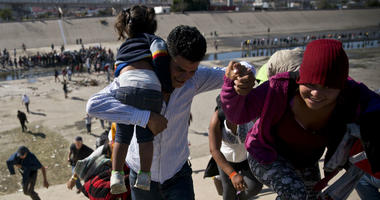 Migrants walk up a riverbank at the Mexico-U.S. border after getting past a line of Mexican police at the Chaparral border crossing in Tijuana, Mexico, Sunday, Nov. 25, 2018, as they try to reach the U.S.