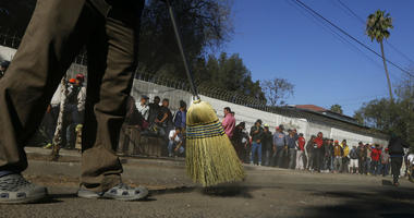 Central American migrants sweep outside the shelter where they are staying in Tijuana, Mexico, Sunday, Nov. 18, 2018.