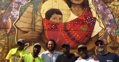 """Chilean artist Ian Pierce (third from left) and his crew worked in partnership with Mural Arts Philadelphia to conceive and create the """"Families Belong Together"""" mural, displayed as a protest to the Trump administration's zero tolerance policy."""